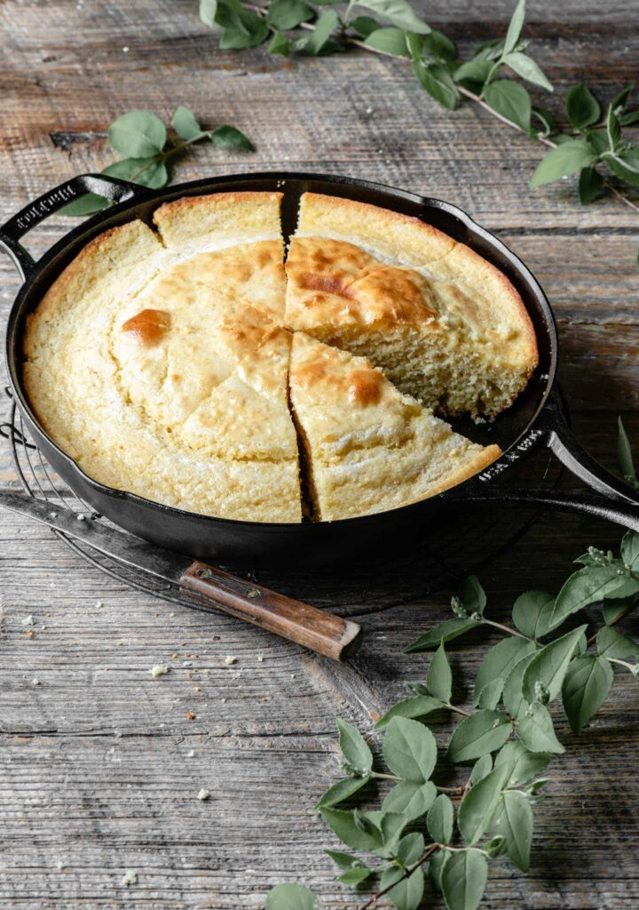 Skillet of Cornbread with a slice missing.