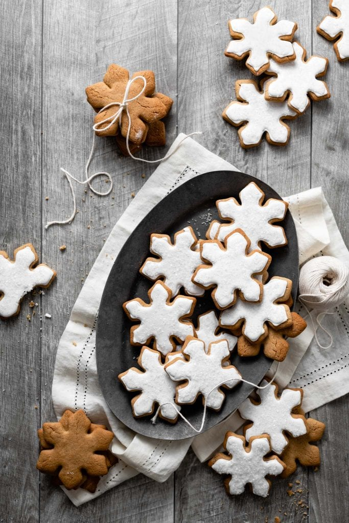Tray of cookies shaped like snowflakes on a wood table.