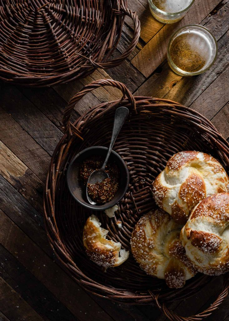 Basket filled with soft pretzels on wooden table.