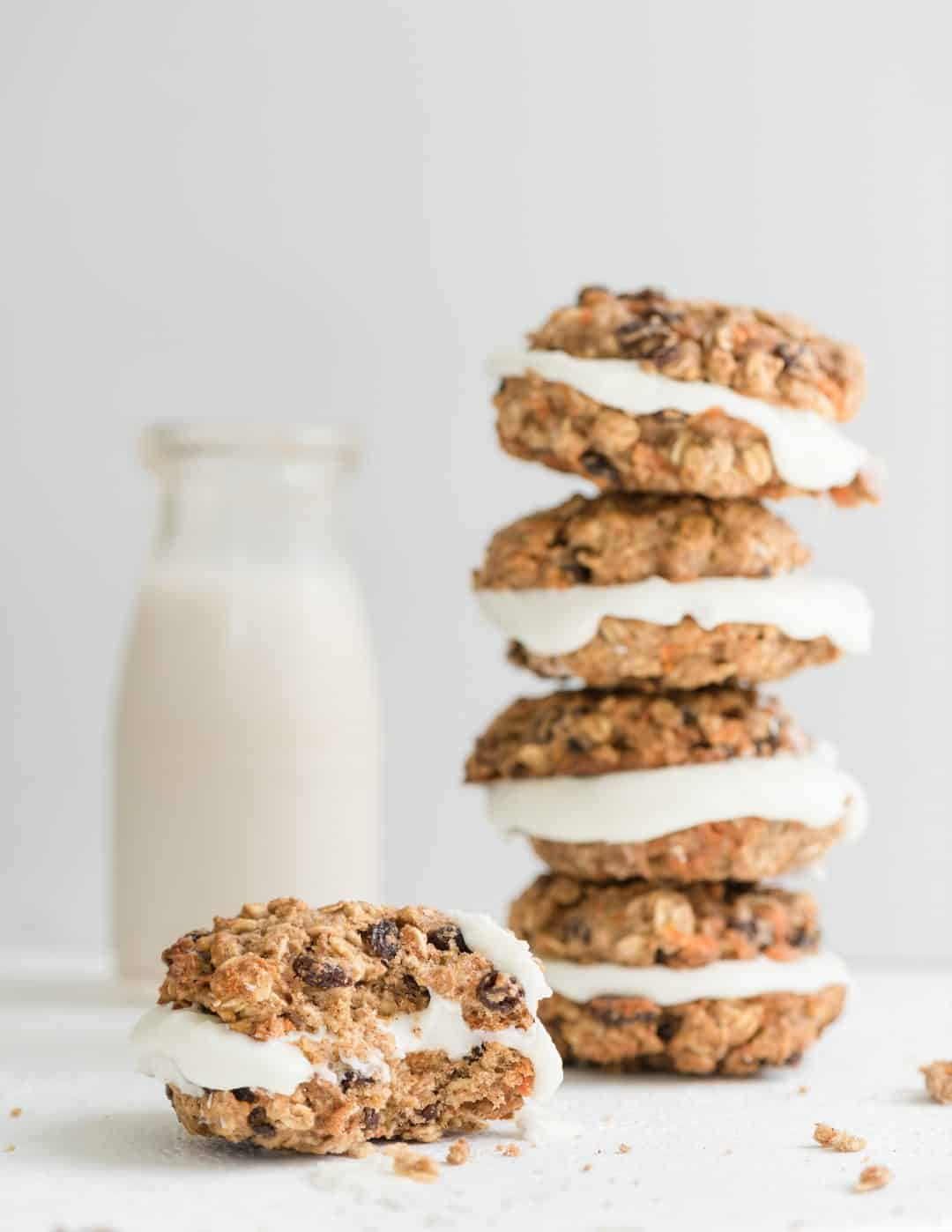 carrot oatmeal cream cookies in a stack with milk
