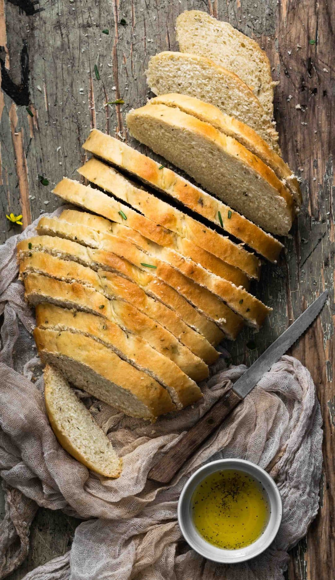 Sliced bread loaf  sprinkled with fresh rosemary on a wooden board.
