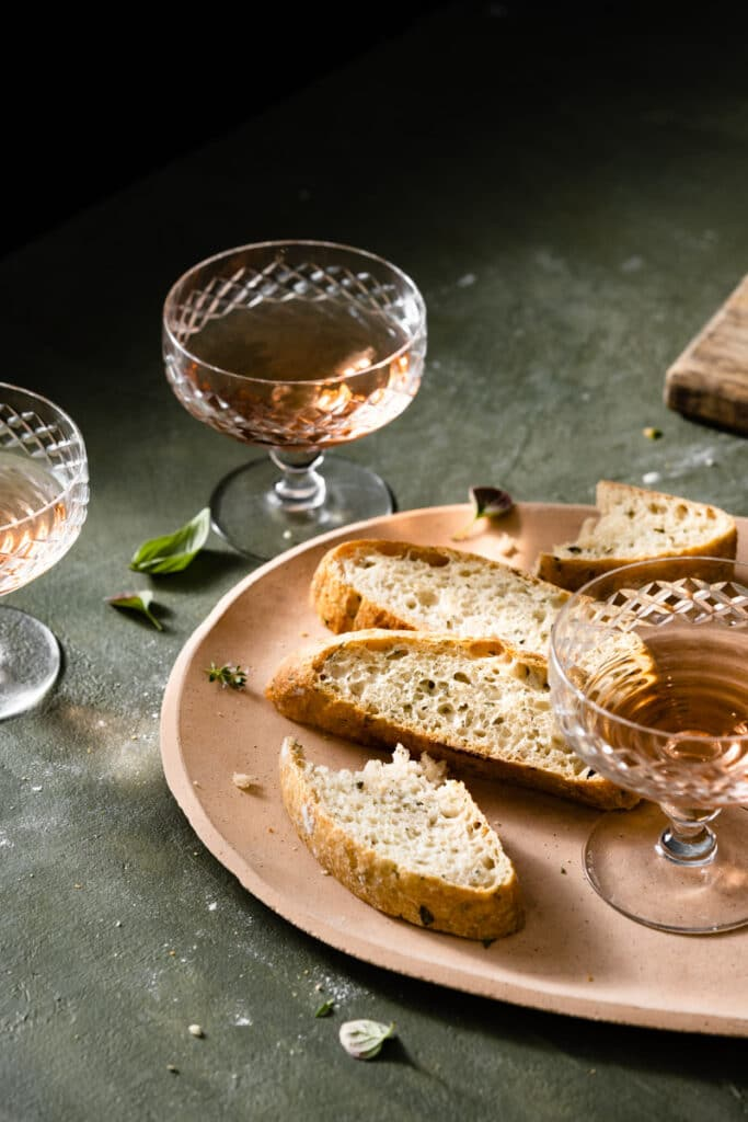 Slices of bread with glasses of pink wine on green table.