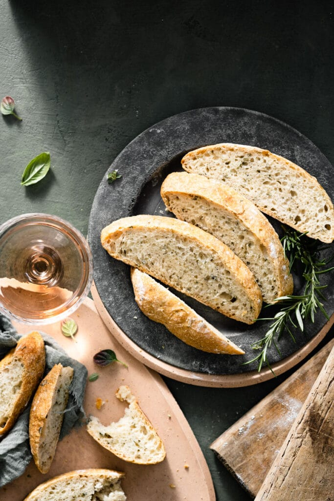 Slices of homemade bread on a plate next to glass of wine.