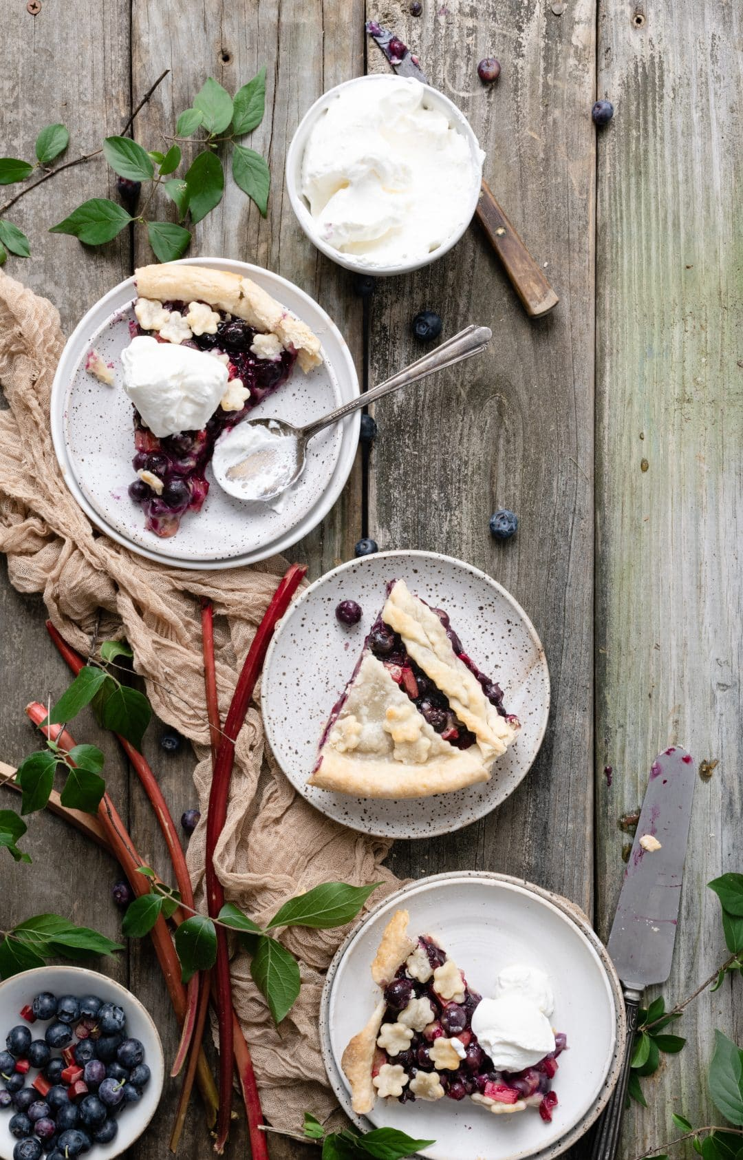 Blueberry Rhubarb Pie slices with whipped cream
