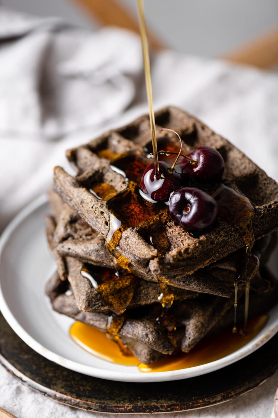 Buckwheat Waffles topped with cherries and maple syrup