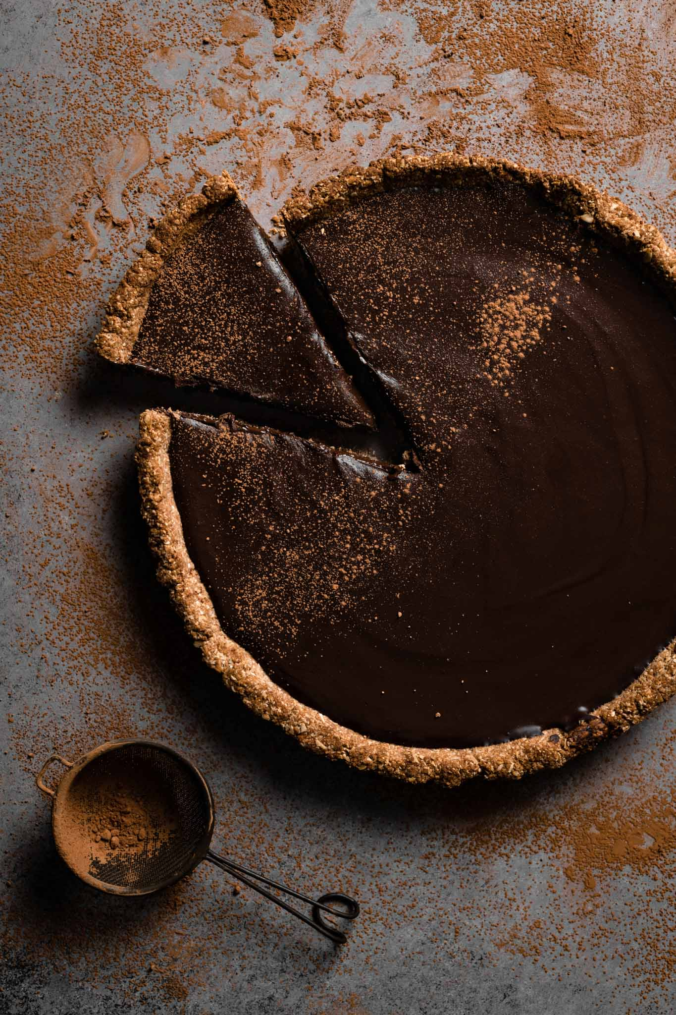 Chocolate tart with chocolate crust sliced.
