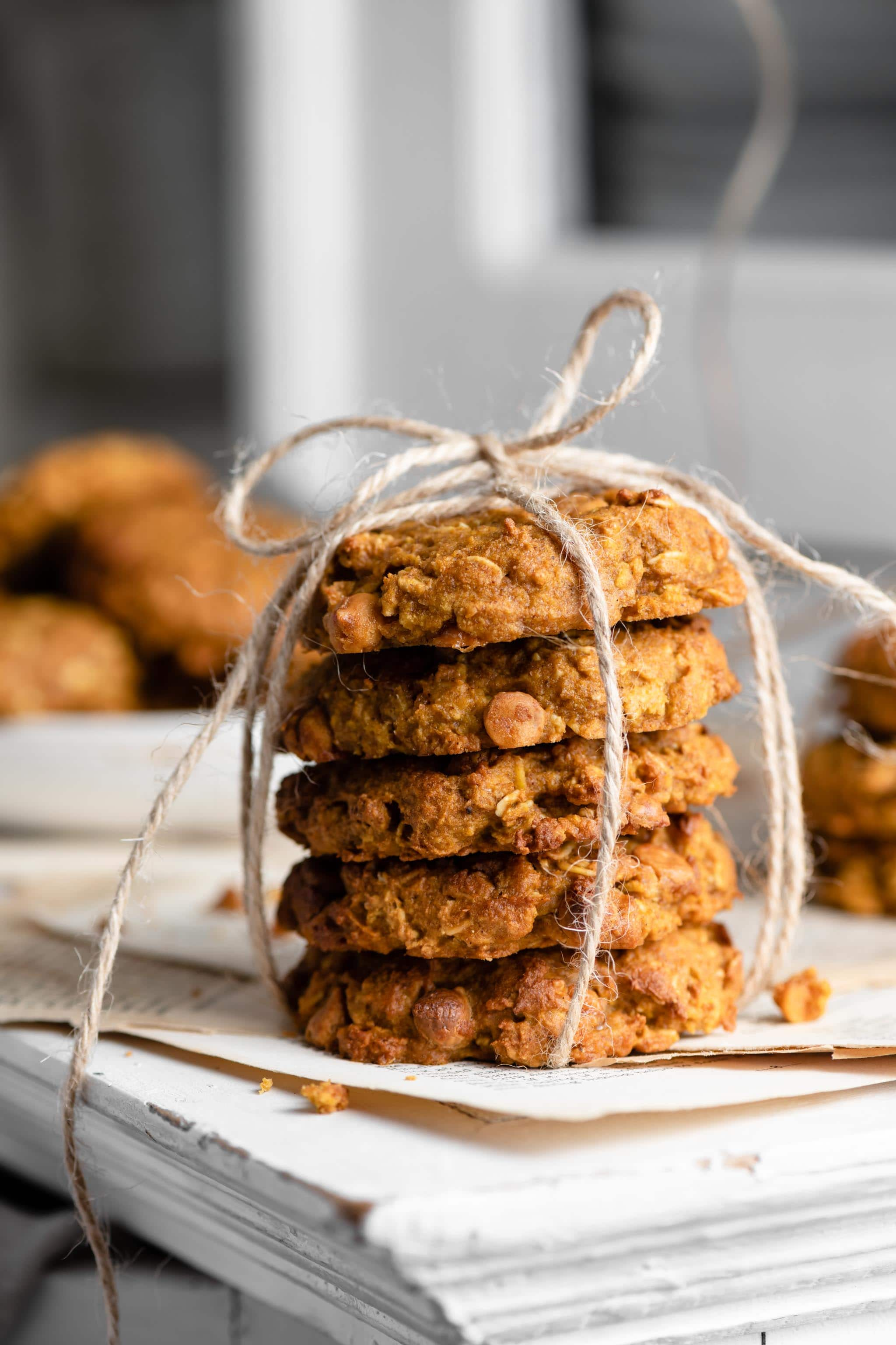 Stack of pumpkin oatmeal cookies ties with twine sitting on white cabinet ledge.