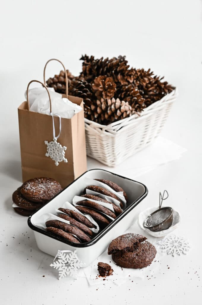 Tin of chocolate cookies on white table next to a brown gift bag and white basket of pine cones.