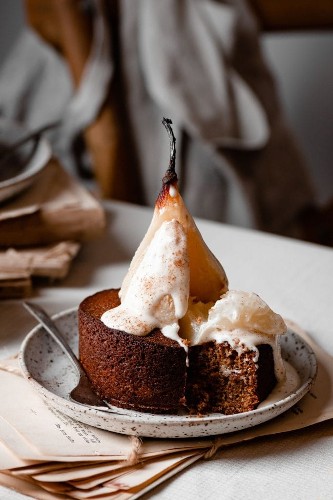 Sliced poached pear covered in cream on a small spice cake.