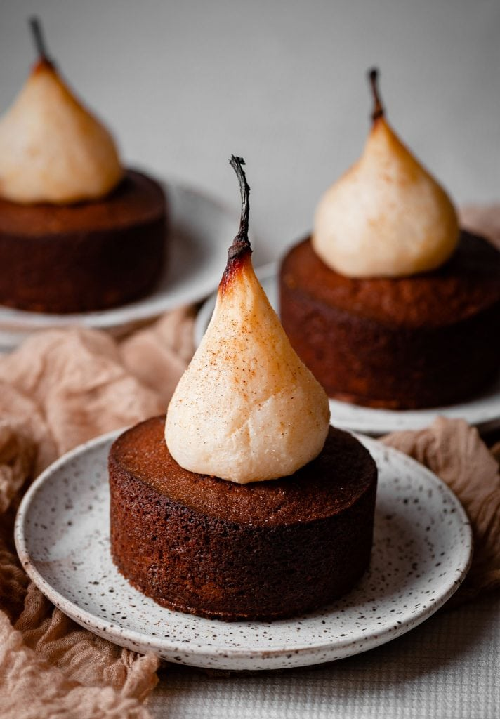 Poached pears on top of mini spice cakes.