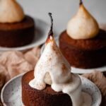 Poached pears on mini cakes covered in cream.