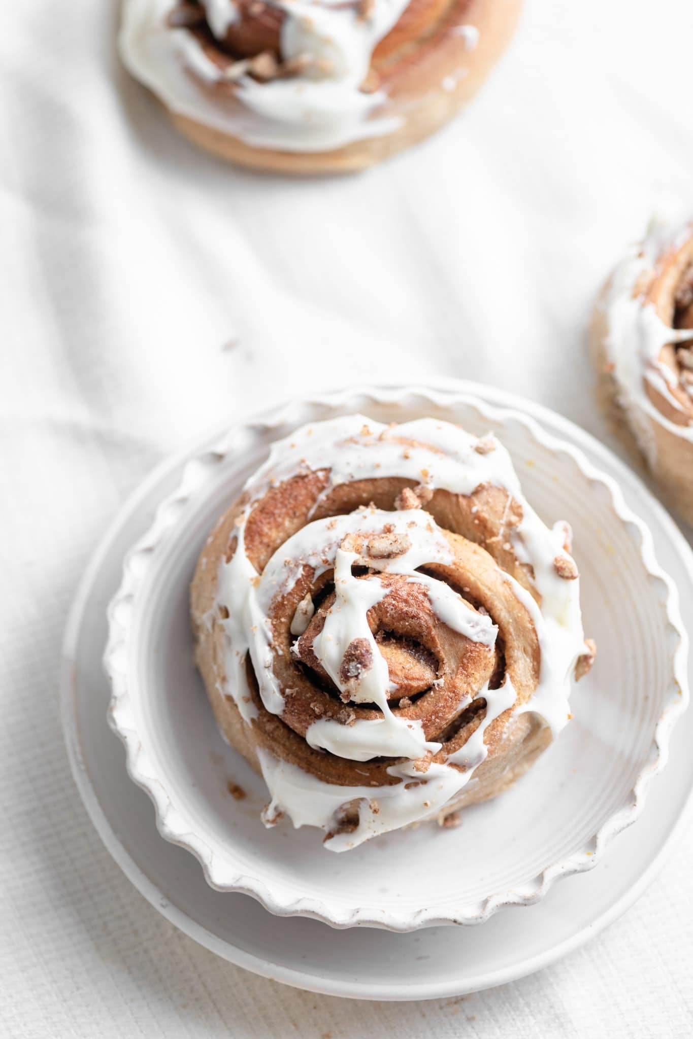 cream cheese frosted cinnamon roll with candied pecans