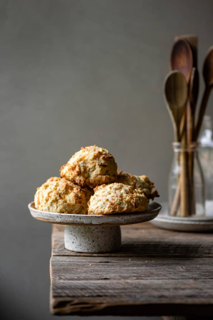 Cake stand topped with cheddar biscuits on a wood table.