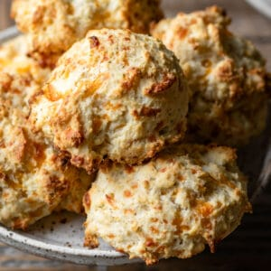 Close up of cheddar biscuits on a white plate.