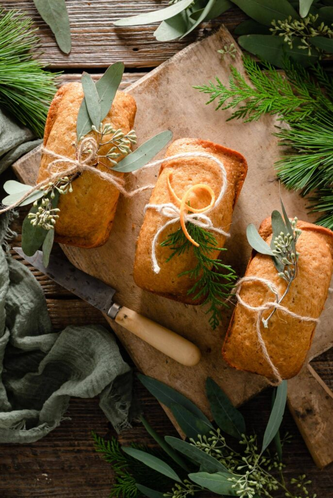 Three orange cakes on cutting board wrapped with greenery.