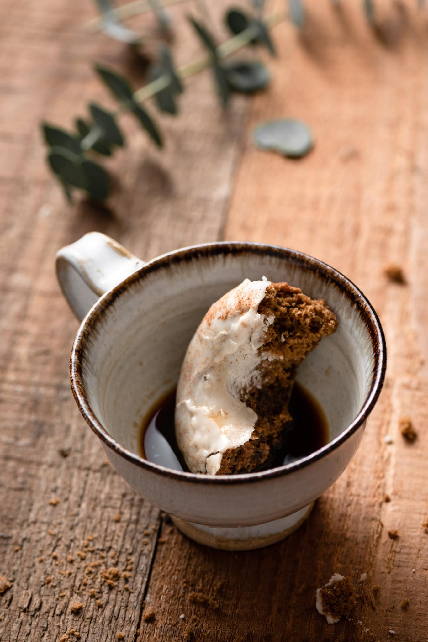 Gingerbread doughnut dunked into a cup of gingerbread coffee.