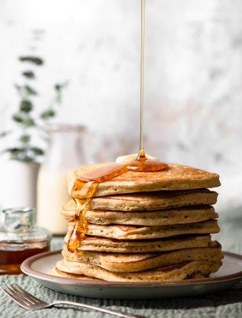 Stack of Cinnamon Eggnog Pancakes with maple syrup
