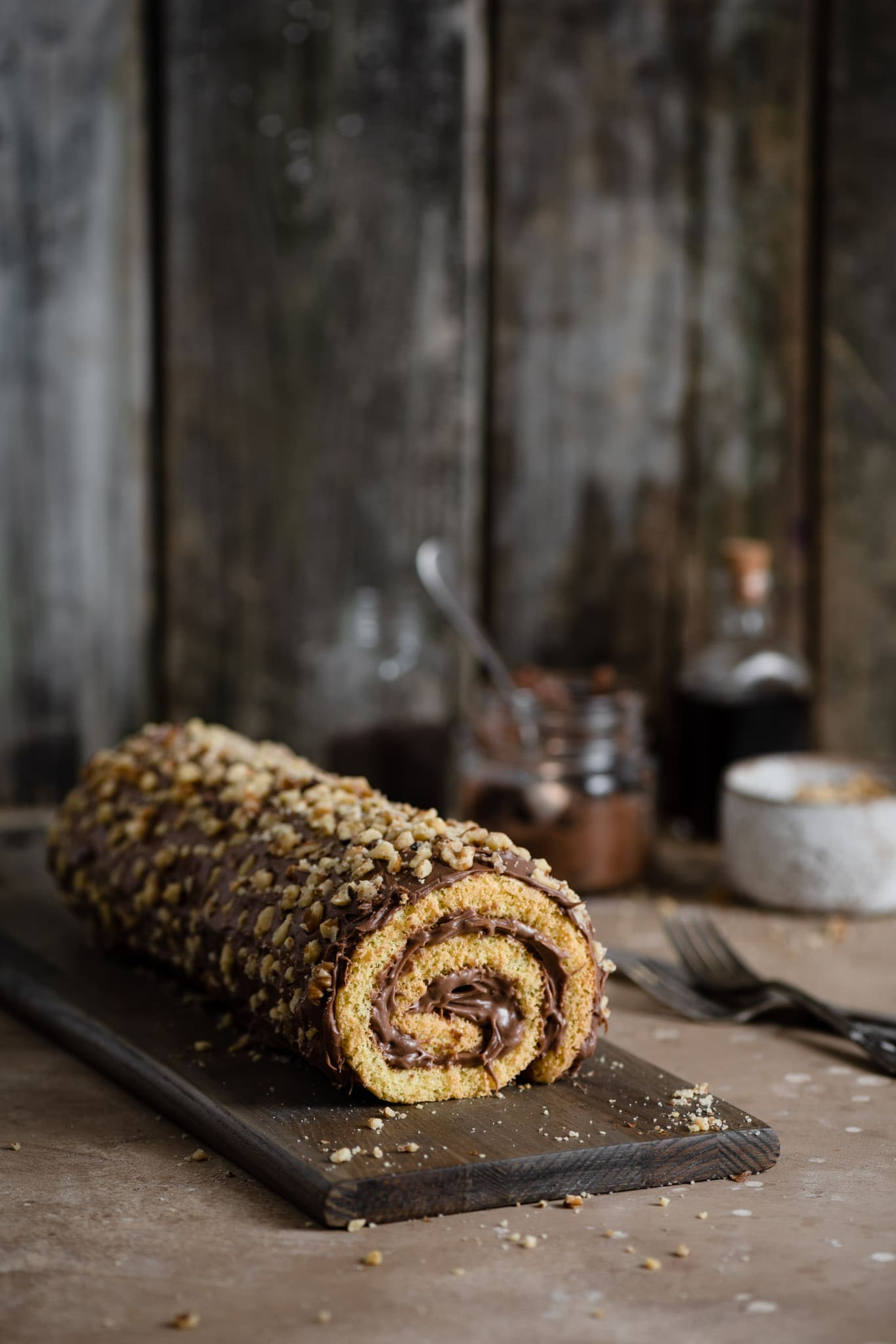 Swiss Roll with chocolate frosting and chopped walnuts.