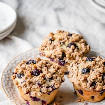 Three blueberry muffins on a plate.