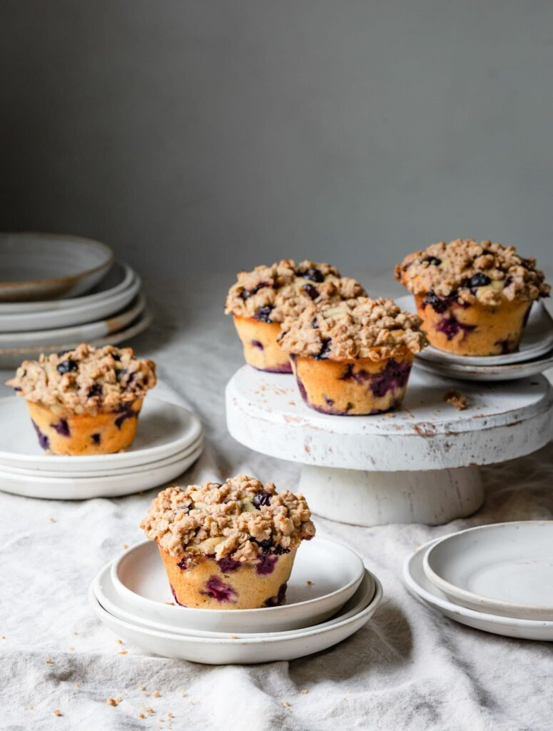 Blueberry muffins on plates and cake stand.