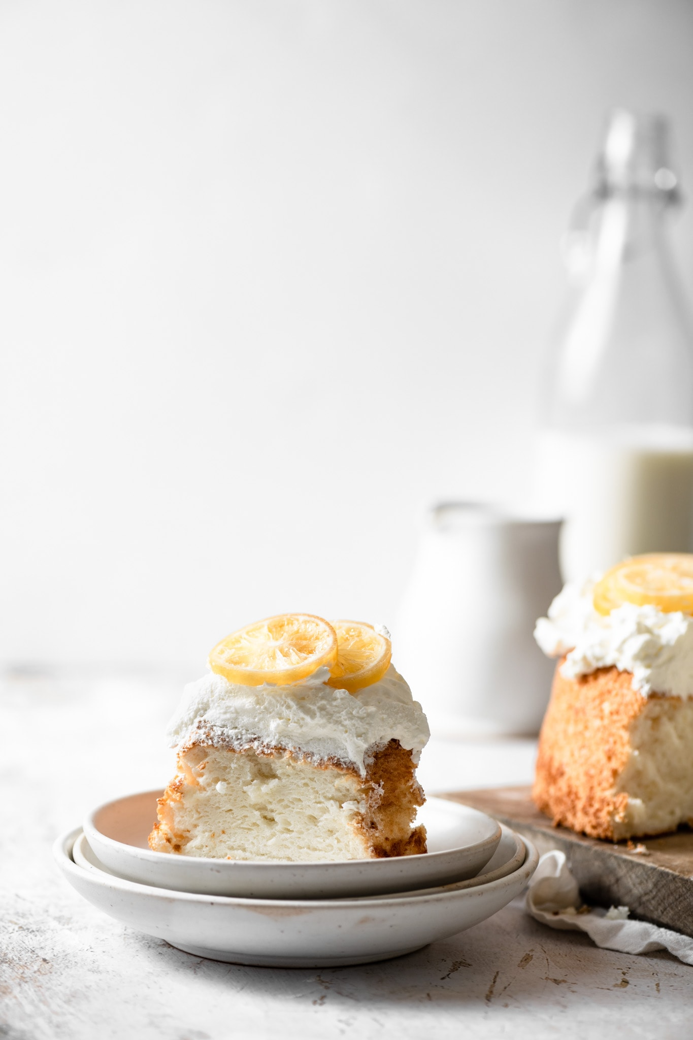 Angel Food Cake with candied lemons and glass of milk.