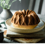 Bundt cake on table with flowers.