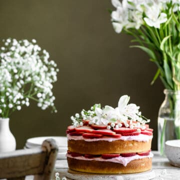 Two layer cake topped with strawberries on white table with flowers.