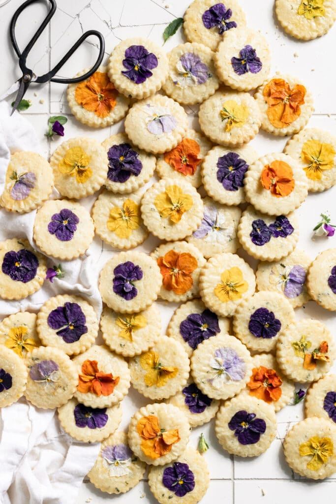 Cookies baked with edible flowers stacked on a white table.