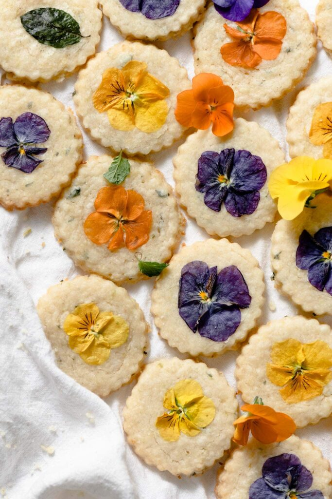 Shortbread cookies topped with colorful edible flowers on white linen.