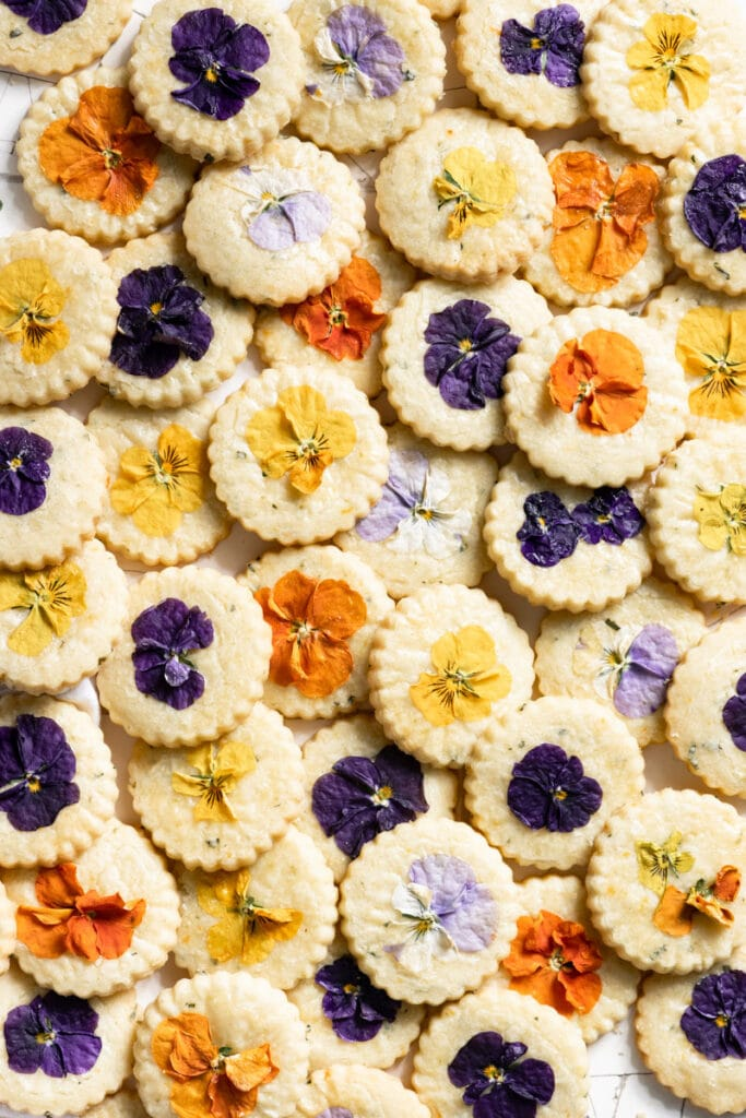 Overlapping shortbread cookies topped with different colored pansies.