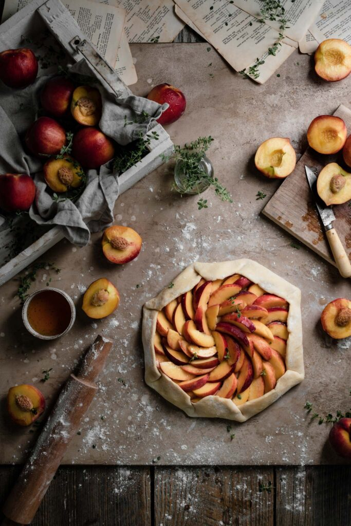 Open face peach pie before baking on a table with sliced peaches.