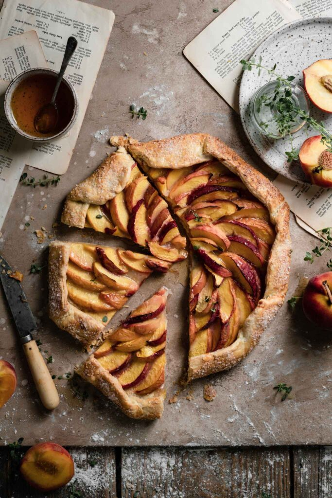 Baked open face peach galette with a bowl of honey on table.