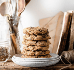 Stack of chewy oatmeal cookies on kitchen shelf.