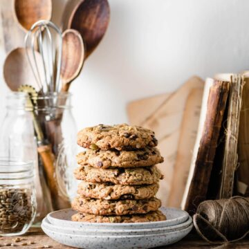 Stack of cookies on plate on kitchen shelf.