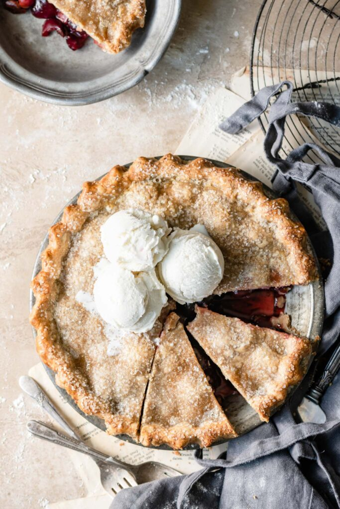 Cherry Pie with three scoops of vanilla ice cream on top and two pieces sliced.