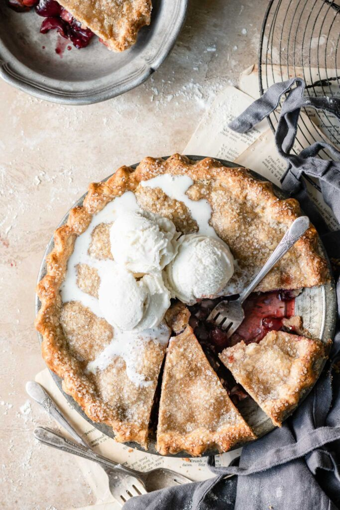 Cherry Pie topped with melted ice cream and a fork cutting a slice from dish.