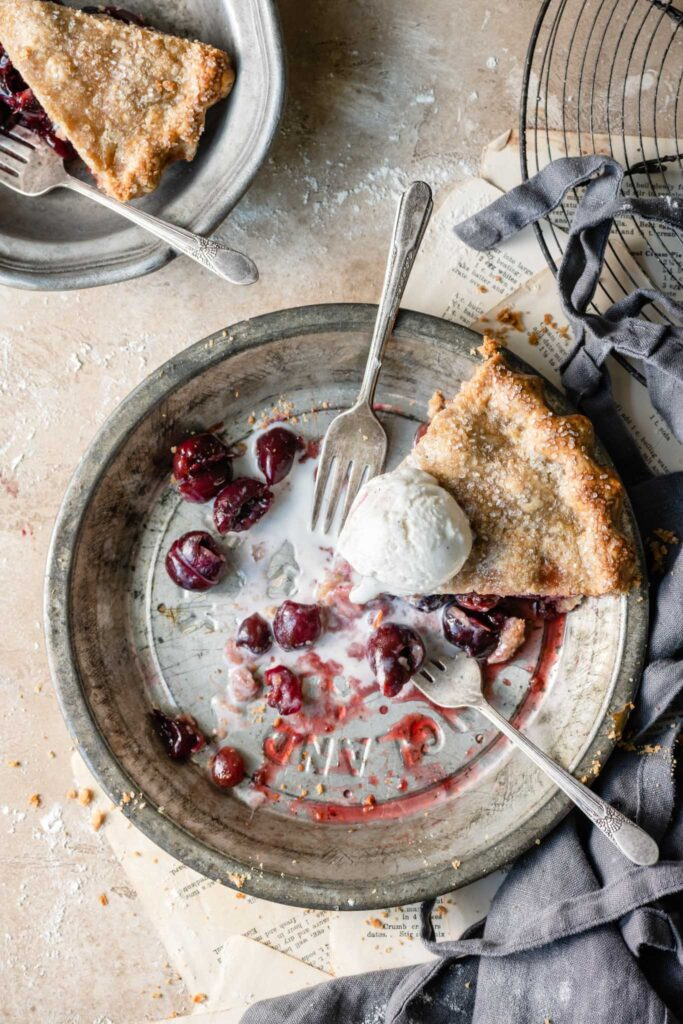 Slice of cherry pie topped with melted vanilla ice cream in a pie dish on table.