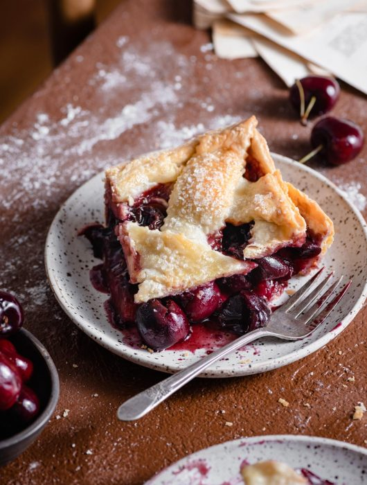 Slice of fresh cherry pie recipe with lattice crust.