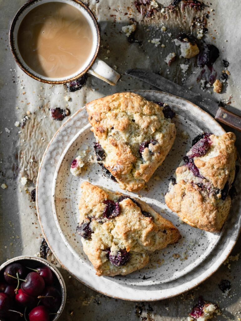 Three cherry scones on a tray with a cup of coffee.