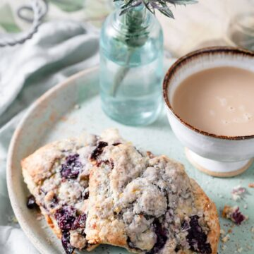 Cherry scones on a plate with cup of coffee.