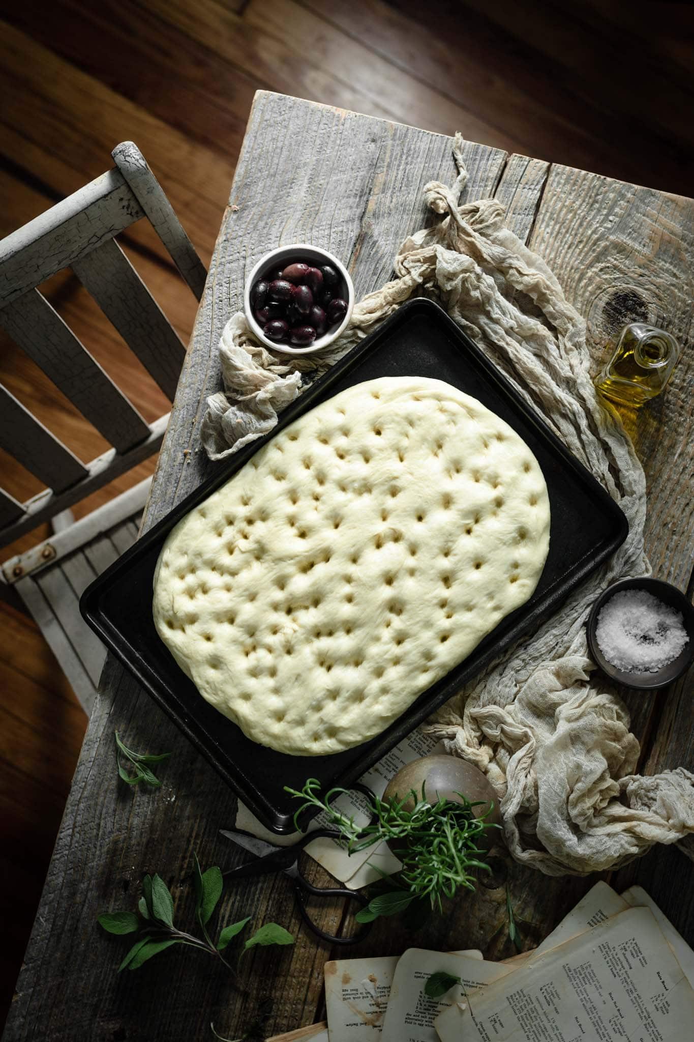 Focaccia bread dough on pan.