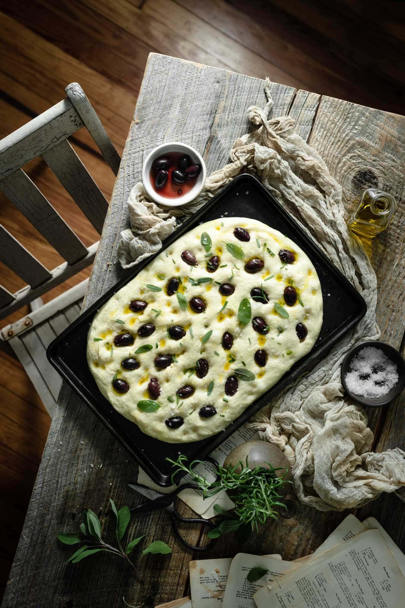focaccia dough with herbs on a pan.