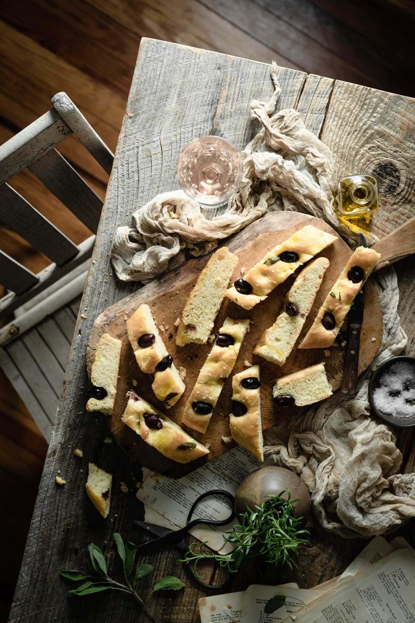 olive bread sliced on cutting board.