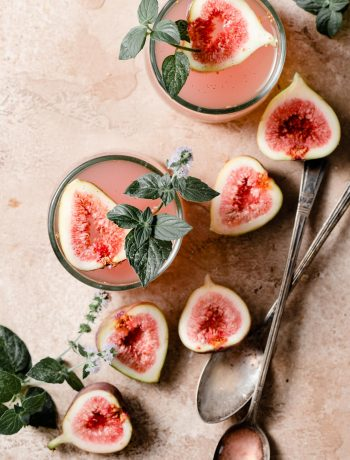 Pink cocktails on table with sliced figs.