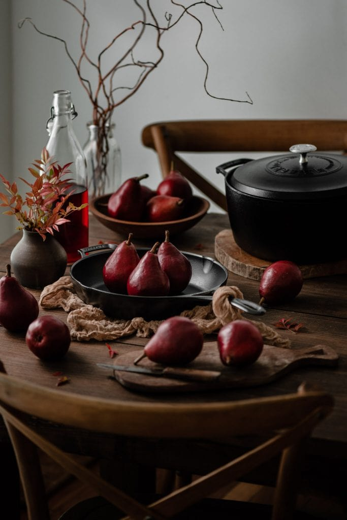 Red Anjou Pears on table with pots and fall decor.