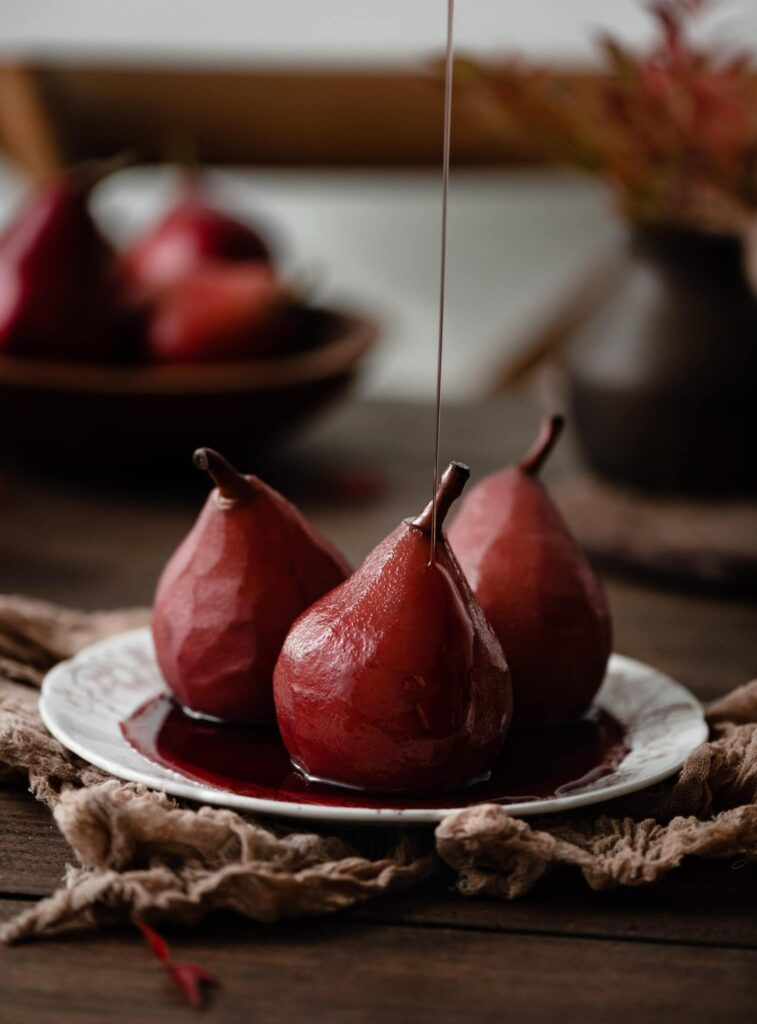 Red wine pears on plate with a drizzle of honey.