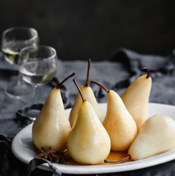 White wine poached pears on table with two glasses of wine.