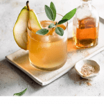 Cocktail with a sliced pear and sage leaf.