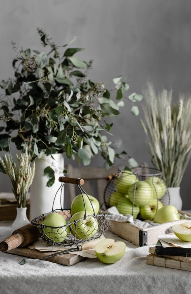 Golden Delicious apples in a fall table setting in wire baskets.