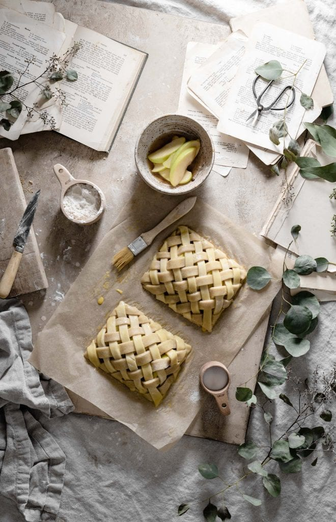 Mini apple pies with lattice crust on table.